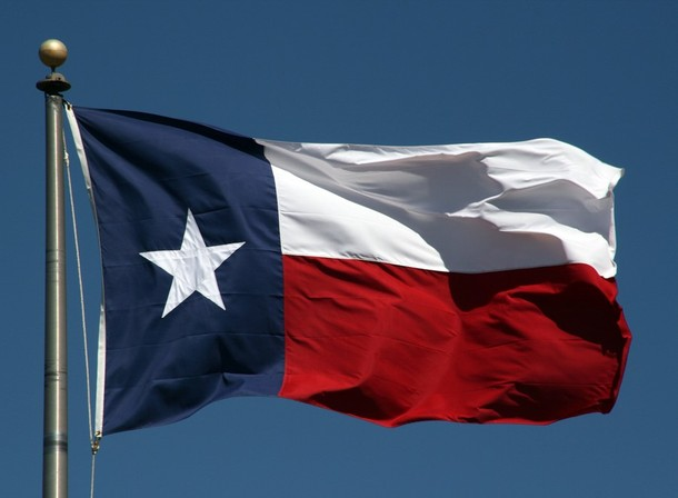 Texas state flag with blue sky in the background.