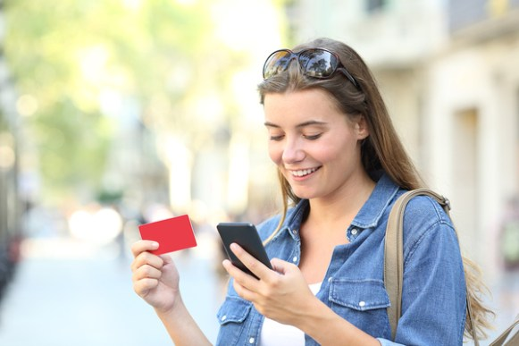 Woman making a purchase with a credit card on her phone.