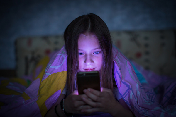 Teenage girl lying down in the dark looking at her smartphone.