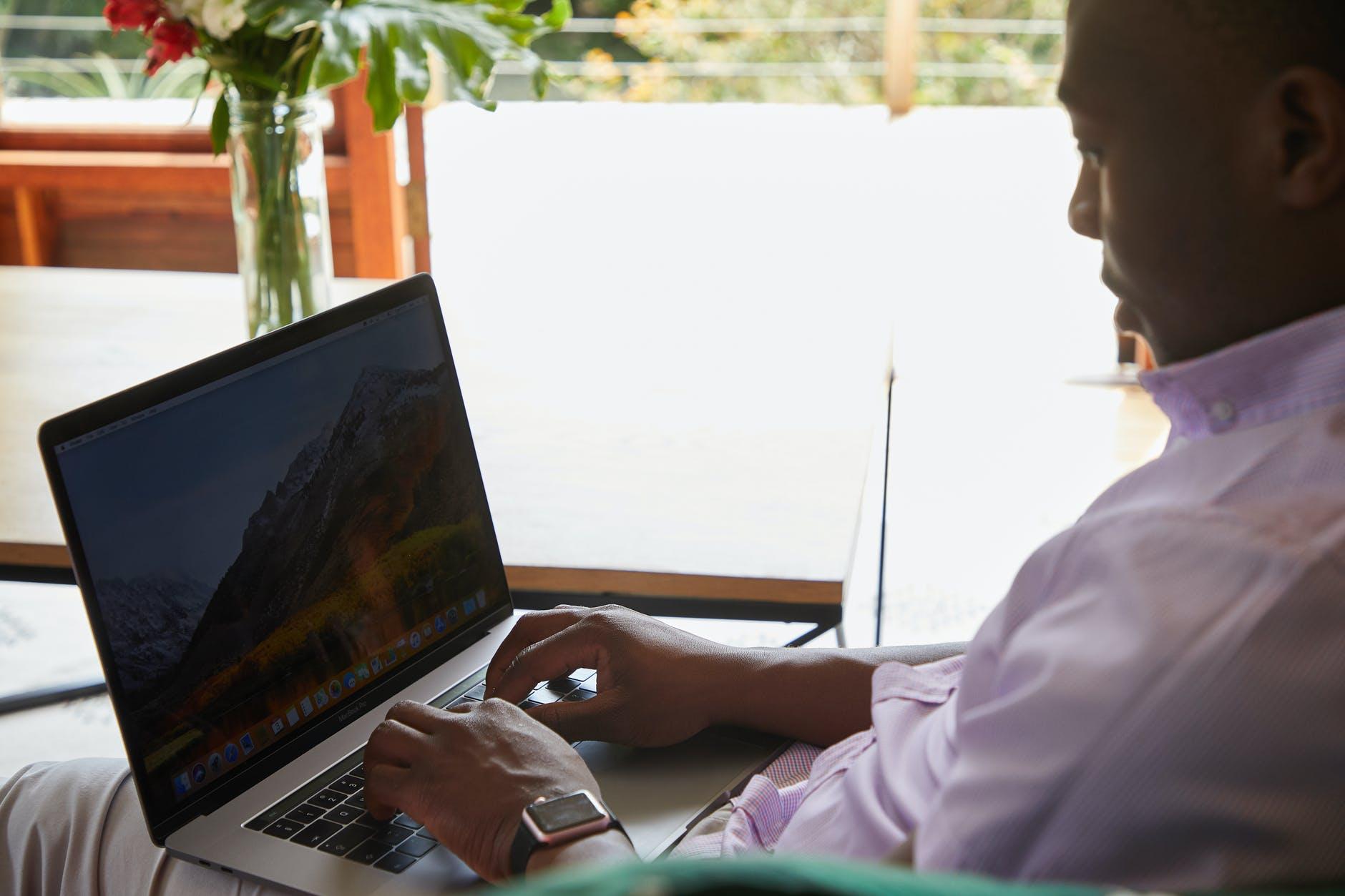 black man with smart watch browsing laptop