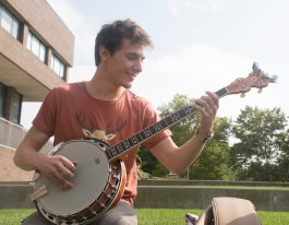 Stony Brook, NY - Joe Schultz, a junior at Stony Brook University, enjoys the sunny weather by playing his banjo out on the Staller Steps. By Joanna Tavares