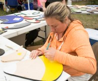 Levittown, NY - Jillian Stiffa, of Bethpage, NY, helps her friend Tom Slattery, of Bethpage, NY, paint wooden signs to sell at the Country Craft Fair at Good Shephard Lutheran Church on Saturday, September 13, 2014. Stiffa draws and paints but she leaves the woodcutting to Slattery.