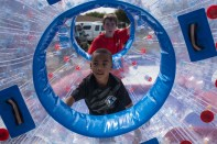 Copiague, NY - Jaiden Lewis of Copiague is working hard to get around in this inflatable human hamster ball at the Long Island Family Festival in Tanner Park on September 14, 2014. He needed a little push from one of the workers at the fair.