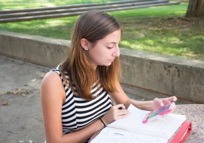 Stony Brook, NY - Kayla Keller, a freshman at Stony Brook University, works on her homework at a table outside Harriman Hall on Friday, September 5, 2014. She has not decided her major yet, but if money was not a factor, she would choose to be a book critic.