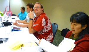"Members of the Hawaii Tribune-Herald bargaining committee caucused during talks Wednesday and Thursday in Honolulu. Management has shown little interest in serious bargaining, refusing to narrow a huge list of takeaway demands including a big jump in health care costs, pay freeze, end of seniority protection against layoff, unfettered right to subcontract two departments and onerous ""social media policy."" From left, Heather Ahue, Derrick DePledge, Colin Stewart and Alicia Tanaka. PMWG photo 2013."