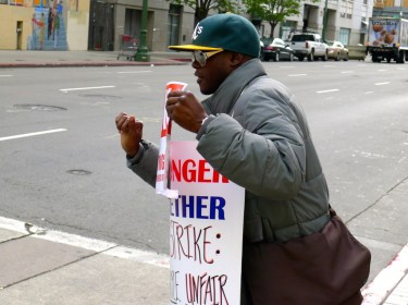 ASLIU member Anthony Brown shows passersby in Oakland why Purple Communications is unfair to its workers. Photo by Local 39521 staff 2014.