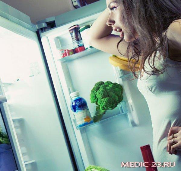 Девушка стоит возле холодильника