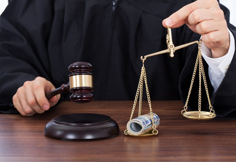 Judge Striking Gavel While Holding Scale With Money
