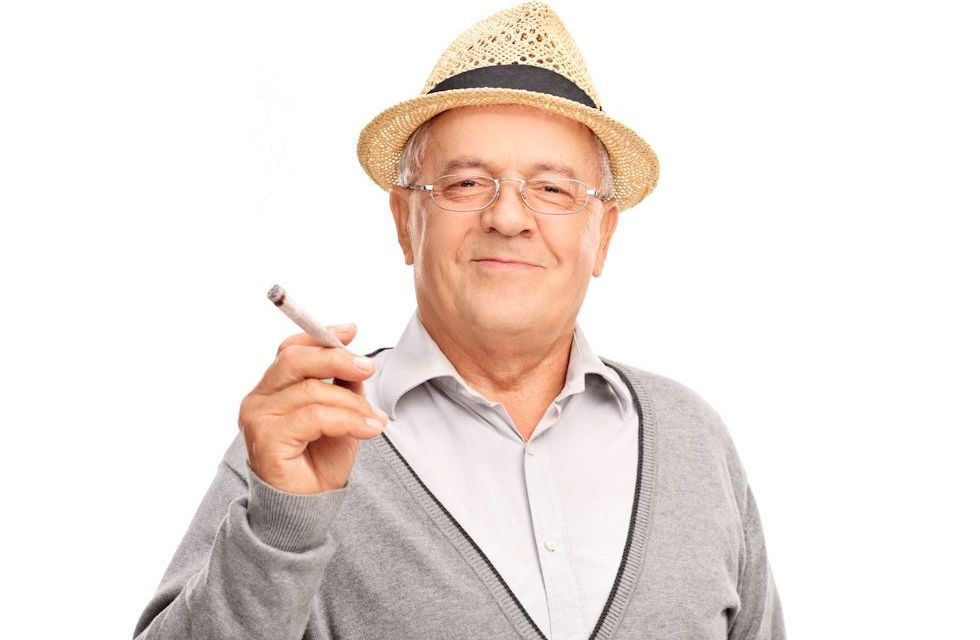 Happy smiling old man enjoying marijuana cigarette
