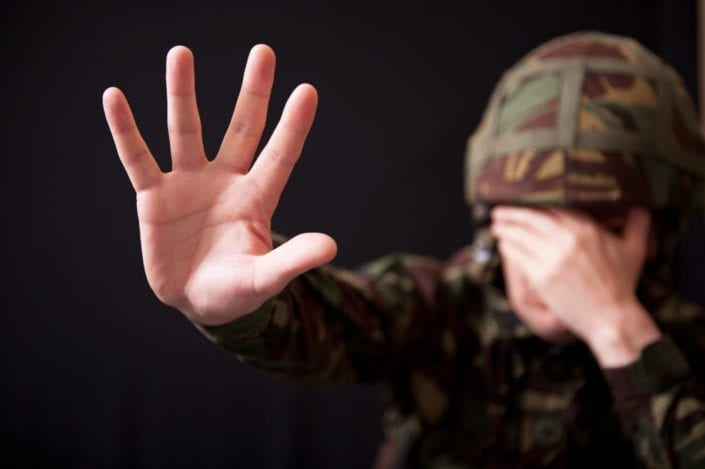 Soldier covering face suffering traumatic experience due to PTSD