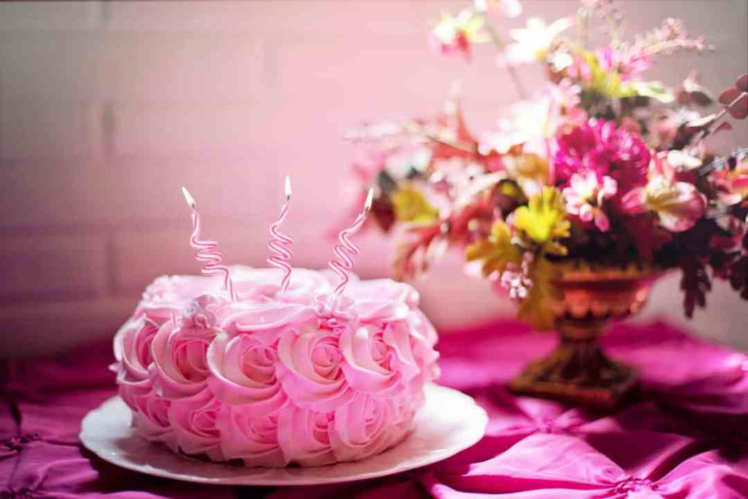 Pink birthday cake with swirly candles indicating you've turned 65 and are eligible for San Diego Medicare Insurance