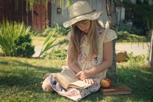 girl in pretty dress reading book on lawn