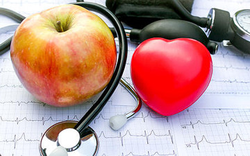 An apple with a heart surrounded by medical equipment