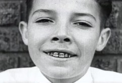 A boy smiles, showing his dirty teeth