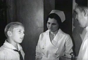 A curious student is greeted by his dentist and a nurse