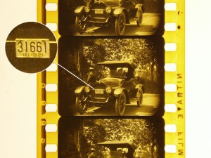 Digitized 16mm film strip from The Reward of Courage highlighting the Rhode Island license plate of an early model automobile.