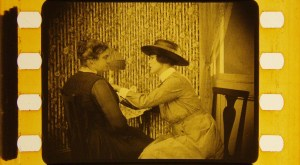 Two women are seated on chairs with the nurse preforming a breast examination.