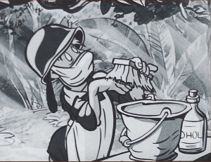 A soldier in a helmet, apron and surgical mask scrubs his hand with a brush.