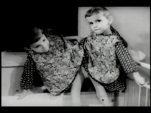 Conjoined twins in dresses stand in a crib.