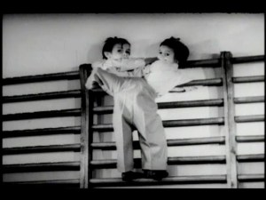 Conjoined twins climb a ladder like structure against a wall.
