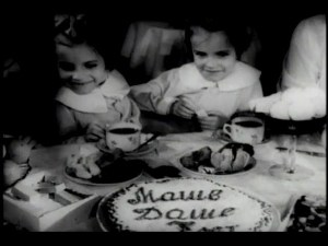 Seven-year-old conjoined twin girls sit at a table spread with cake and tea.