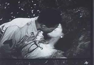a GI and his girl kissing passionately outdoors on the ground.