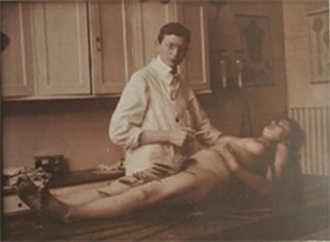 A young man in a white coat stands, scalpel in hand, by an untouched naked female cadaver.