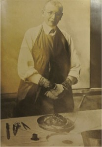 Jakob Erdheim, in his later years, wearing rubber gloves, white shirt, dark tie, white gown partly covered by a black apron behind a table holding surgical instruments and a brain.