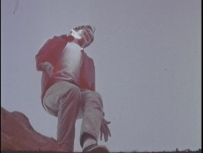 A smiling teenage boy in a red jacket dances at the edge of a cliff