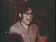 A woman wearing glasses and a houndstooth jacket screams, her mouth open and eyes squeezed shut.
