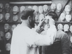 A man fits a soldier with a prosthetic nose attached to glasses.