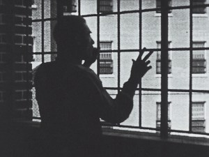 A patient stands in the shadows and gestures out a window.