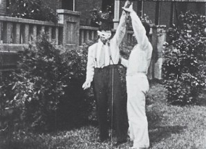 A man in white lifts a patient's arm. The patient wears a white mask.