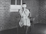 A female patient wearing a white mask sits in front of a brick wall and gestures with her hands clasped under her chin.