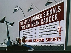 A public health message billboard from the American Cancer Society is visible as Ed and his wife stop for a railway signal.