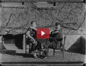 Two people sit outdoor in chairs making similar gestures.