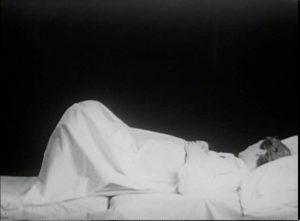 Film still of a woman lying under a white sheet.