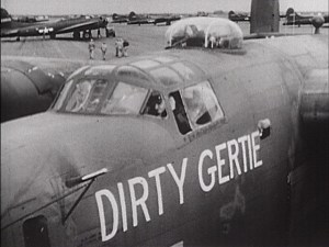 An Airplane on a landing field with Dirty Gertie painted on the side.