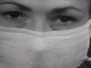 Closeup of a woman's face wearing a surgical mask.