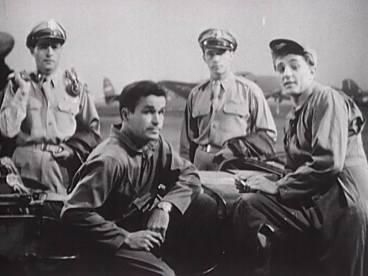 Men in uniform gathered around a jeep.