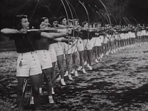 A line of women in uniform practice archery.