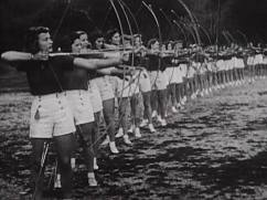A line of women in uniform practice archery.