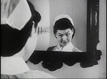 A nurse looks at herself in a mirror.