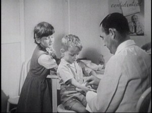 A doctor prepares a young boy for an injection while an older girl looks on.
