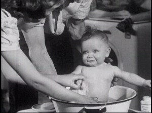 A woman gives a baby a bath in a basin.