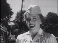 A woman in a nurses uniform laughing outdoors.