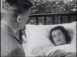 A man in a suit looks down at a woman in a hospital bed.
