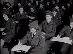 Women in army uniforms writing in a classroom.