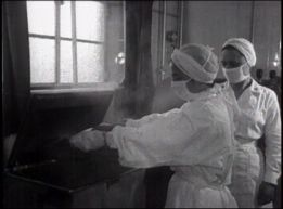 Two women in surgical clothes working.