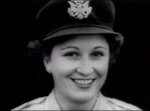 A smiling woman in an army uniform hat.